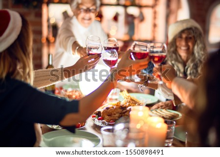 Beautiful group of women smiling happy and confident. Eating roasted turkey and toasting with cup of wine celebrating christmas at home #1550898491