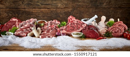 Panorama with assorted raw meat for a winter BBQ displayed on snow against a rustic wood background with copy space suitable for butchery advertising