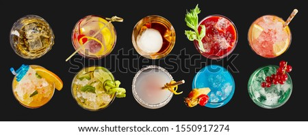 Panorama banner with an assortment of colorful exotic alcoholic cocktails served in glasses with garnishes viewed in two neat lines top down on black #1550917274