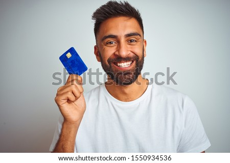 Young indian customer man holding credit card standing over isolated white background with a happy face standing and smiling with a confident smile showing teeth