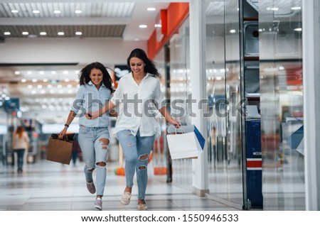 Two young women have fun and running. Having shopping day together in the supermarket. #1550946533
