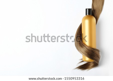 Shampoo bottle wrapped in lock of hair isolated on white, top view. Natural cosmetic products Royalty-Free Stock Photo #1550953316