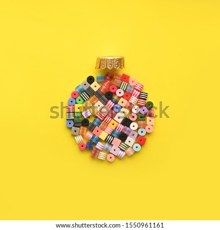 Christmas Bauble made of decoration elements on yellow background. Flat lay. Contemporary design. Contemporary art. Creative conceptual and colorful collage. #1550961161