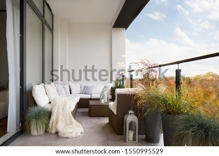 Elegant decorated balcony with rattan outdoor furniture, bright pillows and plants Royalty-Free Stock Photo #1550995529