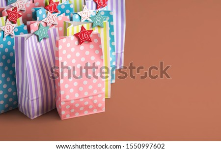 Colorful paper bags with star-shaped numbers for Advent calendar concept, on a brown background. Christmas traditional Advent calendar with 24 gifts. #1550997602