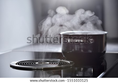 Modern electric induction cooker with built-in ventilation and extractor hood which draws steam from boiling water in a pan. Steam from a boiling pot is drawn into the integrated range hood #1551033125
