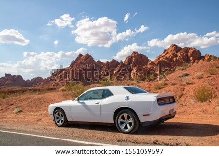 Valley of Fire, Nevada, USA - July 2019: White Dodge Challenger in front of red rocks in the Valley of Fire. #1551059597
