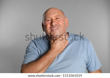 Mature man suffering from throat pain on light grey background #1551061019