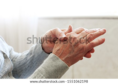 Elderly woman applying moisturizing lotion cream on hand palm, easing aches. Senior old lady experiencing severe arthritis rheumatics pains, massaging, warming up arm. Close up, copy space, background #1551062198