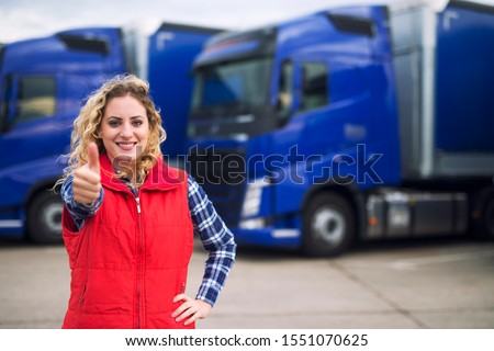 Truck driver occupation. Woman commercial vehicle driver in casual clothes holding thumbs up in front of truck vehicles. Transportation service. #1551070625