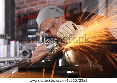 man work in home workshop garage with angle grinder, goggles and construction gloves, sanding metal makes sparks closeup, diy and craft concept Royalty-Free Stock Photo #1551072356