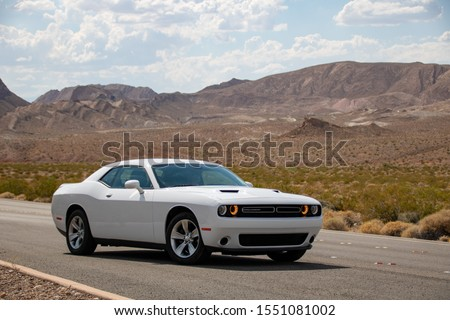 Las Vegas, Nevada, USA - July 2019: White Dodge Challenger with mountain desert landscape in the back. #1551081002