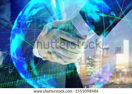 Double exposure of financial chart and world map on cityscape background with two businessmen handshake. Concept of international investment #1551098486