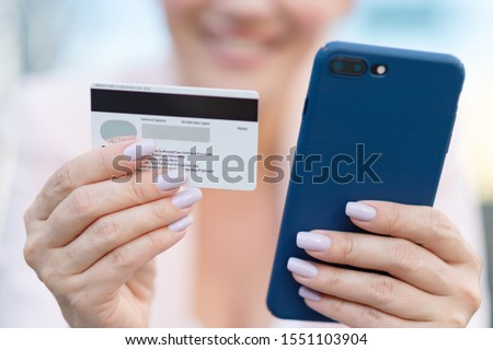 Businesswoman with a credit card and phone makes purchasing outdoors. Successful  woman is using smart phone and bank card for online shopping. Beautiful smiling white woman holds card and cell phone #1551103904