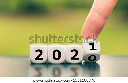 "Hand turns a dice and changes the year ""2020"" to ""2021"". #1551108770"