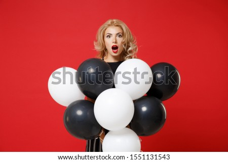 Shocked young woman girl in black clothes posing isolated on red background. New Year 2020 birthday holiday party concept. Mock up copy space. Celebrating holding air balloons keeping mouth wide open #1551131543
