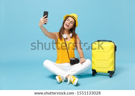 Traveler tourist woman in yellow casual clothes hat with suitcase photo camera isolated on blue background. Female passenger traveling abroad travel on weekends getaway. Air flight journey concept #1551133028