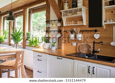 Interior of kitchen in rustic style with vintage kitchen ware and window. White furniture and wooden decor in bright indoor. Country style. Royalty-Free Stock Photo #1551144479