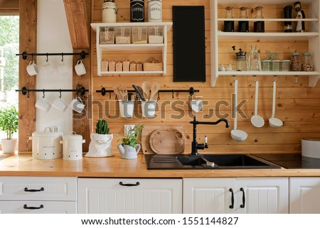 Interior of kitchen in rustic style with vintage kitchen ware and wooden wall. White furniture and wooden decor in bright cottage indoor. Royalty-Free Stock Photo #1551144827