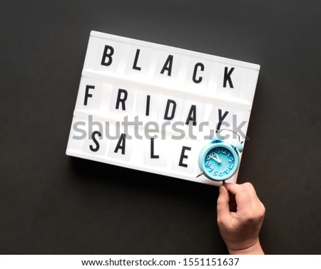 """Lightbox text """"Black Friday Sale"""" on black paper background. Creative flat lay with hand holding alarm clock on the light box. #1551151637"""