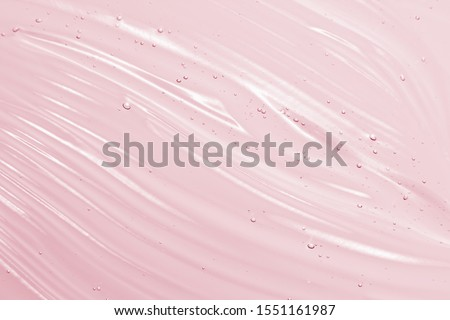 Cosmetic gel background. Face serum, clear beauty cream texture. Pink colored transparent skincare product close-up #1551161987