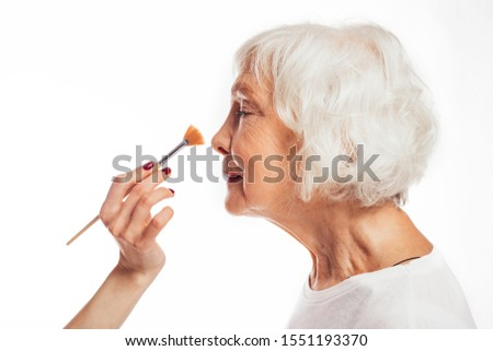 Side view of old senior female model stand calm peaceful and quiet. Young hand hold make-up brush. Woman with grey hair prepares. Isolated over white background stock photo