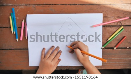 Child draws a pencil drawing of the house and his family. New home. #1551198164