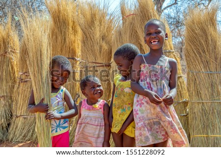 Group of few happy girls and a boy playing with the thatching grass in a village in Botswana #1551228092