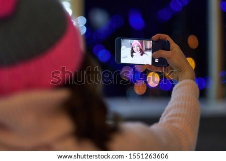 Woman taking selfie on background of night winter city #1551263606