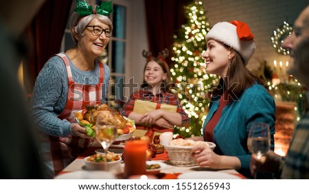 Merry Christmas! Happy family are having dinner at home. Celebration holiday and togetherness near tree. #1551265943
