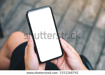 Top view mockup image of a woman holding a black mobile phone with blank white desktop screen  #1551268742