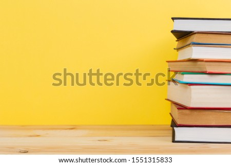 Simple Simple composition of many hardback books, unprocessed books on a wooden table and a yellow background. back to school. Copy space. Education. #1551315833