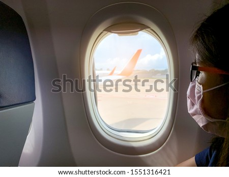 Sick woman wear face mask sit on passenger economy seat near cabin window in airplane. Passenger in departure flight plane at the airport. Novel coronavirus (2019-nCoV) infection  or Wuhan coronavirus Royalty-Free Stock Photo #1551316421