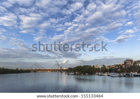 Panoramic photograph of Belgrade and Sava river with the New railroad bridge, made at dusk, from the lower tip of Ada Ciganlija river isle.