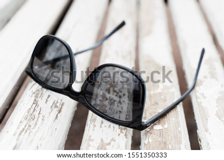 Sunglasses on a wooden bench #1551350333
