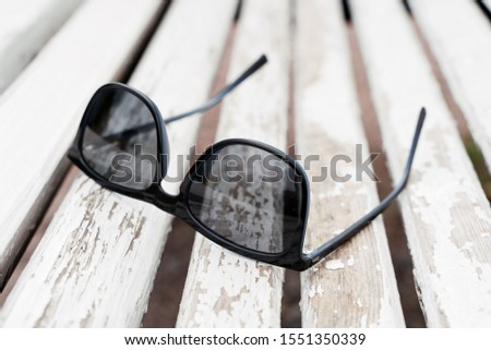 Sunglasses on a wooden bench #1551350339