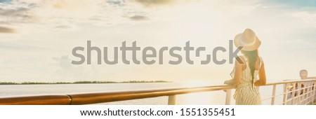 Luxury cruise ship vacation woman elegant tourist woman watching sunset on balcony deck of Europe mediterranean cruising travel destination. Summer vacation cruiseship banner panorama.
