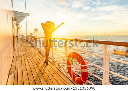 Luxury cruise ship travel elegant woman having fun carefree on deck enjoying watching sunset on Europe cruising destination vacation. Summer european mediterranean cruiseship sailing away on holiday. #1551356090