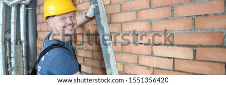 Portrait of man using special construction equipment to remove any concrete masses to make wall made of red brick smooth and easy to plaster surface. Male posing in unfinished room. Building concept #1551356420
