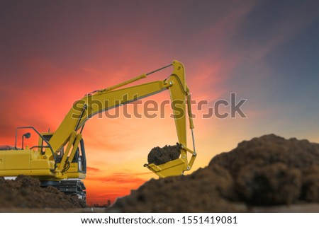 Excavators are digging the soil in the construction site on the sunset background #1551419081