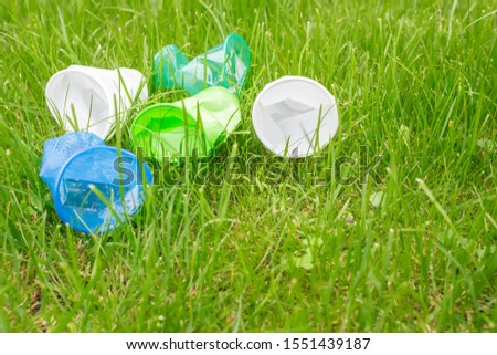 Bright colourful disposable plastic cups isolated on green grass. Ecology problem. Copy space.   #1551439187