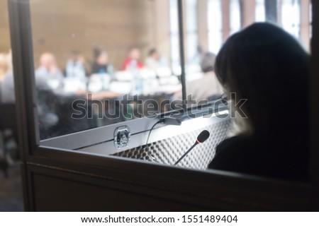 woman translating in translators cubicle Royalty-Free Stock Photo #1551489404