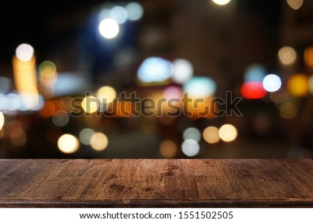 Empty dark wooden table in front of abstract blurred bokeh background of restaurant . can be used for display or montage your products.Mock up for space. #1551502505