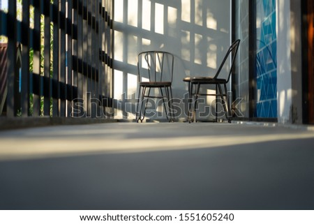 Simple lounge with square shadow and sun light with two chair and one small table spot on the corner. Modern design of lounge and electricity. Taken from low angle and middle angle #1551605240