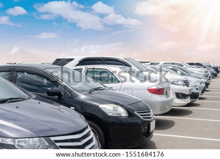 Car parked in large asphalt parking lot with beautiful cloud and blue sky and sun background. Outdoor parking lot  travel transportation technology with nature concept #1551684176