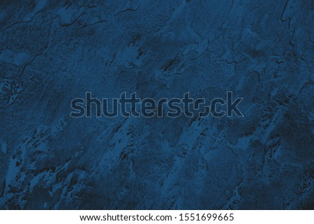 Dark blue colored low contrast stone textured background with roughness and irregularities to your design or product. Color trend concept. #1551699665