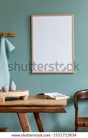 Stylish and minimalistic dining room interior with wooden table, chair, mock up poster frame, fruit tray, book and elegant accessories. Eucalyptus color. Ready to use. Template. Modern home decor.