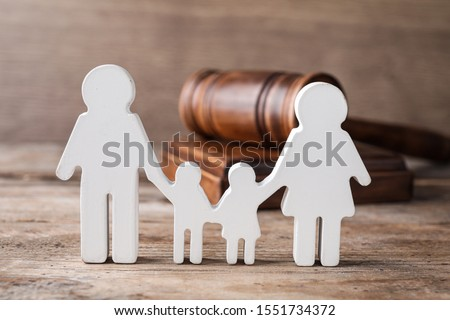 Figure in shape of people and gavel on wooden table. Family law concept #1551734372