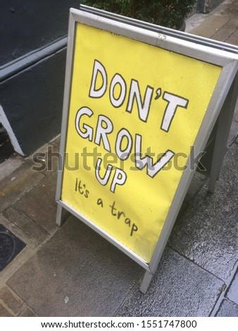 Sign that says Don't Grow Up It's a Trap on a yellow background. #1551747800