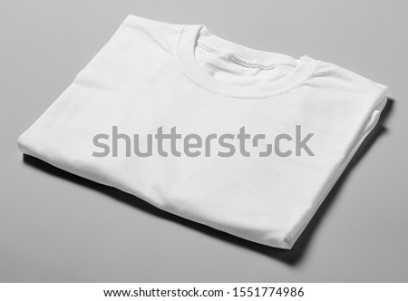 Mockup of isometric perspective white blank folded t-shirt template in studio photo shoot on grey background #1551774986